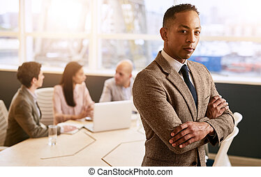 Businessman standing in front of his employees with crossed arms