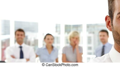 Businessman standing in front of his team