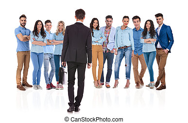 businessman standing in front of his team, looking at them