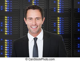 Businessman standing in front of server racks