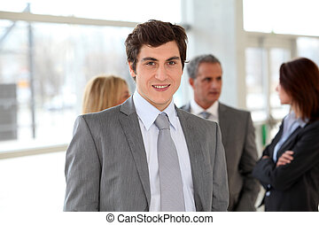Businessman standing in hall in front of group of business people
