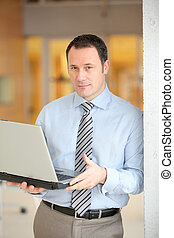 Businessman standing in hall with laptop computer