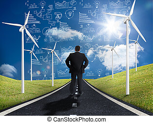 Businessman standing in middle of road with wind turbines...