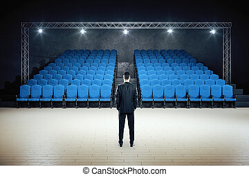 Businessman standing in minimalistic movie theater with blue chairs. Cinema and entertainment concept.