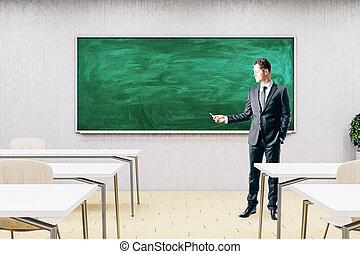 Businessman standing in modern classroom with empty chalkboard