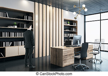 Businessman standing in modern manager's office with bookcase