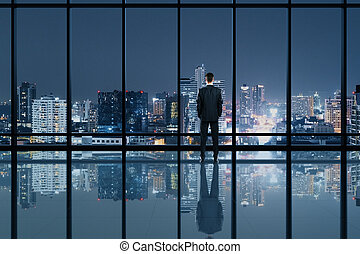 Businessman standing in modern office interior and looking to night city