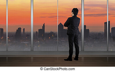 Businessman standing in Office building looking at Cityscape skyline night light