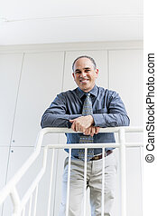 Businessman standing in office hallway smiling