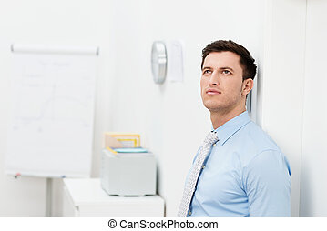 Businessman standing in the office thinking