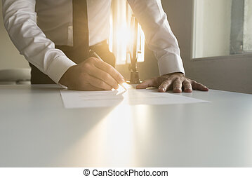 Businessman standing in white shirt and black necktie at office desk signing contract