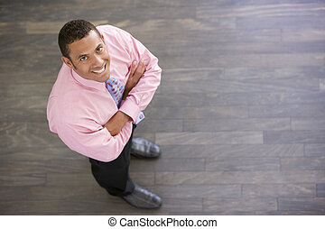 Businessman standing indoors smiling