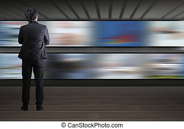 Businessman standing looking at the TV screen