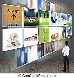 Businessman standing looking at TV screen