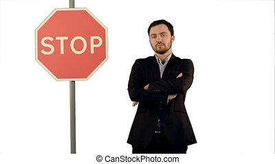 Businessman standing near a stop sign on laptop on white background isolated.
