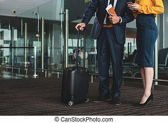 Businessman standing near his assistant in waiting hall
