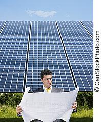 businessman standing near solar panels