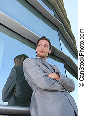 Businessman standing next to window
