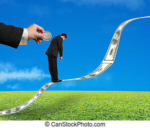 Businessman standing on growing money trend with hand insert coin into back in green meadow and blue sky background