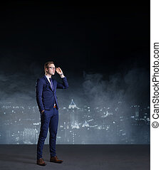 Businessman standing on night city background.  Job, business, career, concept.
