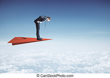 Businessman standing on red paper plane