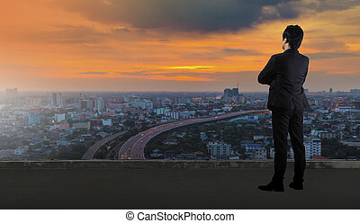 Businessman standing on roof and looking at Cityscape skyline night light