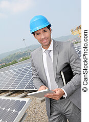 Businessman standing on solar panel installation