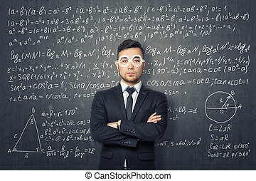 Businessman standing on the background of blackboard with mathematical formulas.