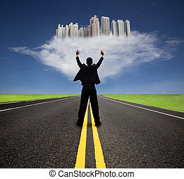 businessman standing on the empty road and watching the ...