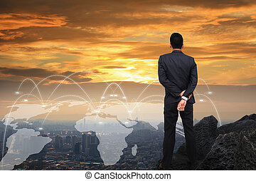 Businessman standing on the hill looking to the city.
