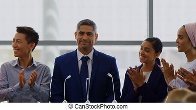 Front view of a Caucasian businessman standing on the podium with his colleagues while the public is applauding him in the business seminar 4k