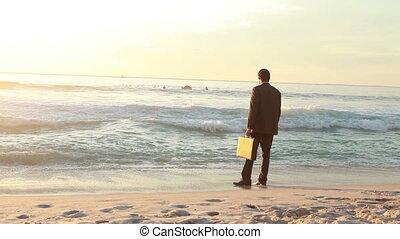 Businessman standing on the shore letting the waves wet him