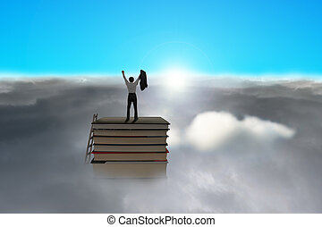 Businessman standing on top of books with cloudy below