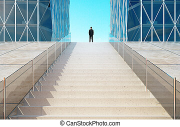 Businessman standing on top of the stairs near the modern business center