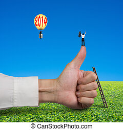 Businessman standing on top of thumb, another in lamp balloon with 2014, meadow and blue sky background