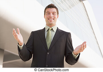 Businessman standing outdoors by building with hands out