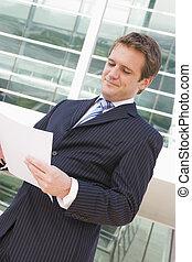 Businessman standing outdoors looking at paperwork