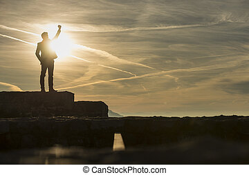 Businessman standing outdoors on a wall with his fist raised against a sun