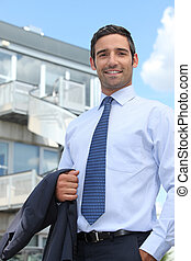 Businessman standing outside an office building