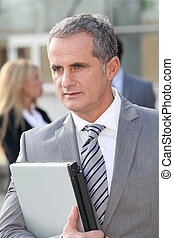 Businessman standing outside with laptop computer