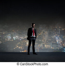 Businessman standing over night city background. Job, business, career, concept.