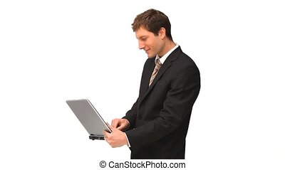 Businessman standing up with a laptop against a white...