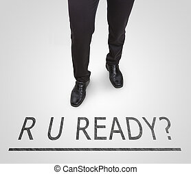 Businessman standing wearing court shoes on ready line.