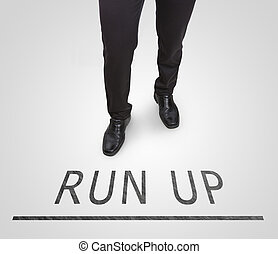 Businessman standing wearing court shoes on run up line.
