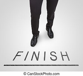 Businessman standing wearing court shoes on finish line.