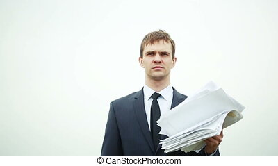 businessman standing with a stack of paper in the wind.
