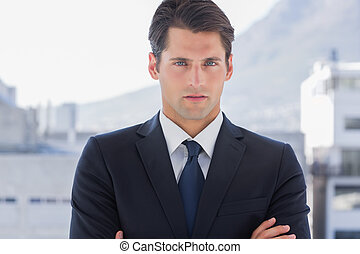 Businessman standing with arms crossed in a bright office