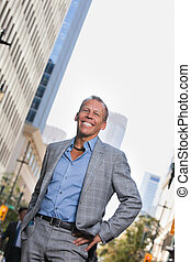 Businessman standing with buildings in background