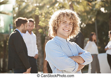 Businessman standing with crossed arms outside smiling