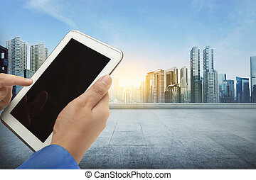 Businessman standing with finger touching screen of a digital tablet